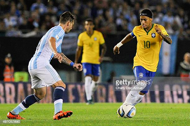 Neymar of Brazil drives the ball as he is marked by Lucas Biglia of Argentina during a match between Argentina and Brazil as part of FIFA 2018 World...