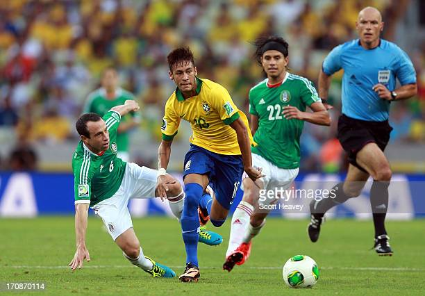 Neymar of Brazil goes past the challenge of Gerardo Torrado of Mexico during the FIFA Confederations Cup Brazil 2013 Group A match between Brazil and...