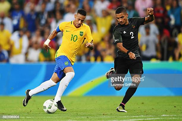 Neymar of Brazil holds off the challenge of Jeremy Toljan of Germany during the Men's Football Final between Brazil and Germany at the Maracana...