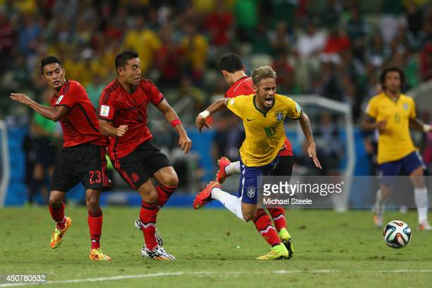 Neymar of Brazil is challenged by Jose Juan Vazquez of Mexico Rafael Marquez and Marco Fabian during the 2014 FIFA World Cup Brazil Group A match...