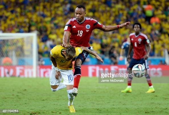 Neymar of Brazil is challenged by Juan Camilo Zuniga of Colombia during the 2014 FIFA World Cup Brazil Quarter Final match between Brazil and...