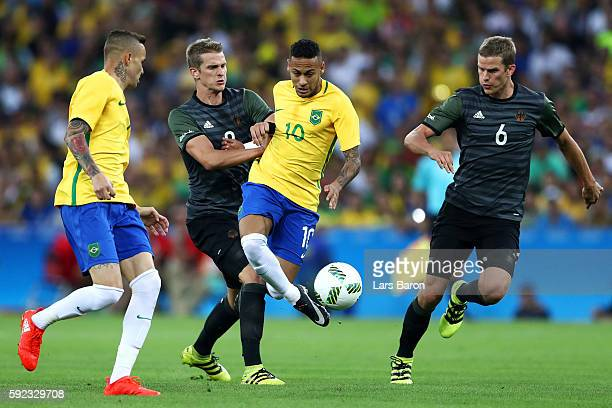 Neymar of Brazil is challenged by Lars Bender of Germany and Sven Bender of Germany during the Men's Football Final between Brazil and Germany at the...
