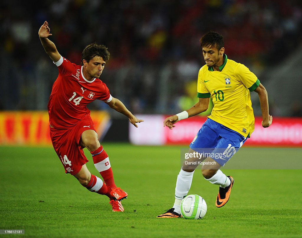 Neymar of Brazil (R) is challenged by <a gi-track='captionPersonalityLinkClicked' href=/galleries/search?phrase=Valentin+Stocker&family=editorial&specificpeople=5522265 ng-click='$event.stopPropagation()'>Valentin Stocker</a> of Switzerland during the international friendly match between Switzerland and Brazil at St. Jakob Stadium on August 14, 2013 in Basel, Switzerland.