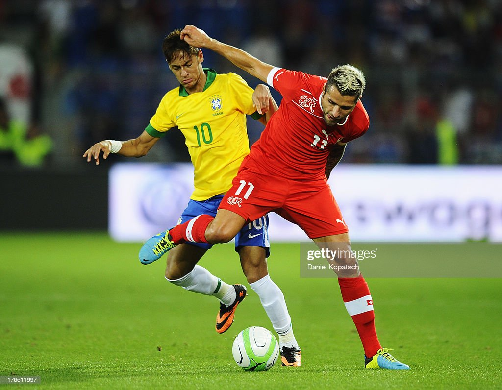 Neymar of Brazil is challenged by <a gi-track='captionPersonalityLinkClicked' href=/galleries/search?phrase=Valon+Behrami&family=editorial&specificpeople=453450 ng-click='$event.stopPropagation()'>Valon Behrami</a> of Switzerland during the international friendly match between Switzerland and Brazil at St. Jakob Stadium on August 14, 2013 in Basel, Switzerland.