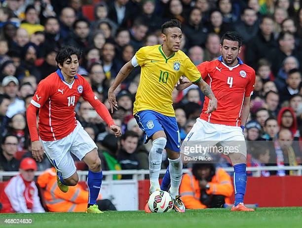 Neymar of Brazil is closed down by Matias Fernandez and Mauricio Isla of Chila during the International Friendly match between Brazil and Chile at...