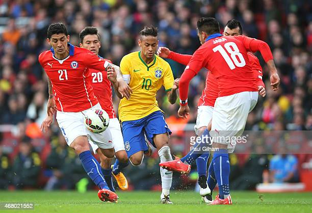 Neymar of Brazil is closed down by Pablo Hernandez Charles Aranguiz Gonzalo Jara and Gary Medel of Chile during the international friendly match...