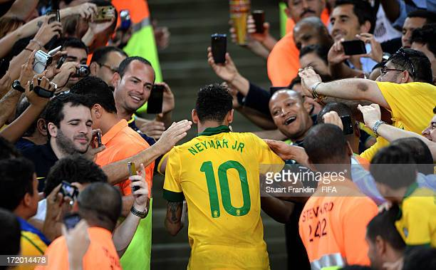 Neymar of Brazil is congratulated by fans at the end of the FIFA Confederations Cup Brazil 2013 Final match between Brazil and Spain at Maracana on...