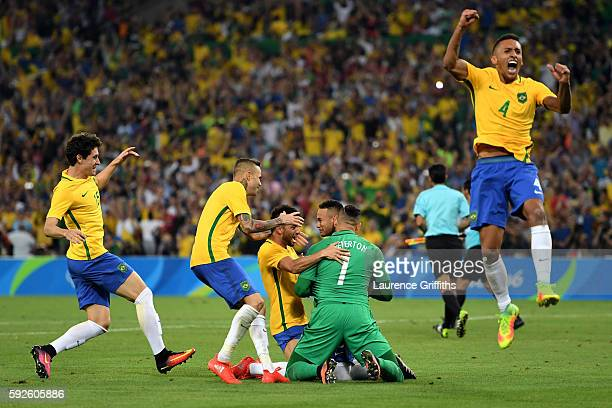 Neymar of Brazil is surrounded by team mates as he celebrates after scoring the winning penalty in the penalty shoot out during the Men's Football...