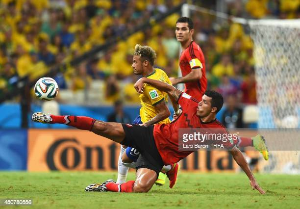 Neymar of Brazil is tackled by Francisco Javier Rodriguez of Mexico during the 2014 FIFA World Cup Brazil Group A match between Brazil and Mexico at...