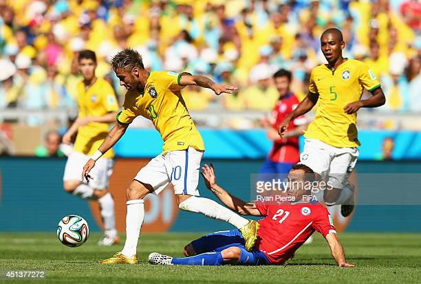 Neymar of Brazil is tackled by Marcelo Diaz of Chile during the 2014 FIFA World Cup Brazil Round of 16 match between Brazil and Chile at Estadio...