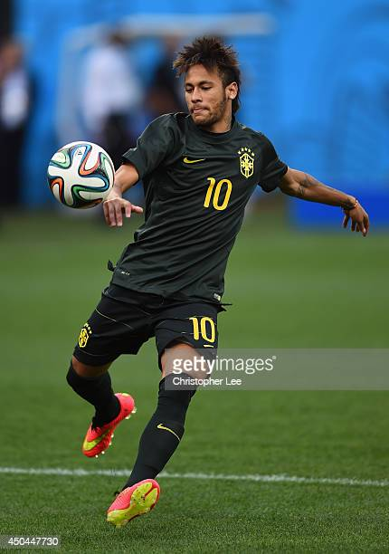Neymar of Brazil kicks the ball during a Brazil training session ahead of the 2014 FIFA World Cup Brazil opening match against Croatia at Arena de...