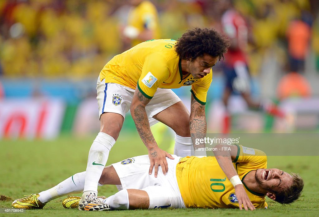 Neymar of Brazil lies injured while Marcelo of Brazil appeals during the 2014 FIFA World Cup Brazil Quarter Final match between Brazil and Colombia at Estadio Castelao on July 4, 2014 in Fortaleza, Brazil.