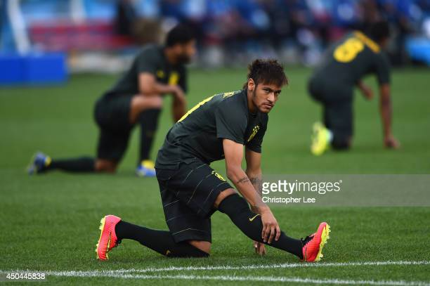 Neymar of Brazil looks on during a Brazil training session ahead of the 2014 FIFA World Cup Brazil opening match against Croatia at Arena de Sao...