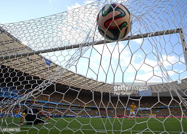 Neymar of Brazil scores during a penalty shootout past Claudio Bravo of Chile during the 2014 FIFA World Cup Brazil round of 16 match between Brazil...
