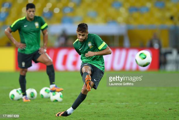 Neymar of Brazil shoots as Hulk looks on during a training session ahead of their FIFA Confederations Cup Brazil 2013 Final match against Spain at...