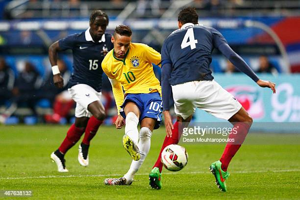 Neymar of Brazil shoots on goal in front of Raphael Varane and Bacary Sagna of France during the International Friendly match between France and...