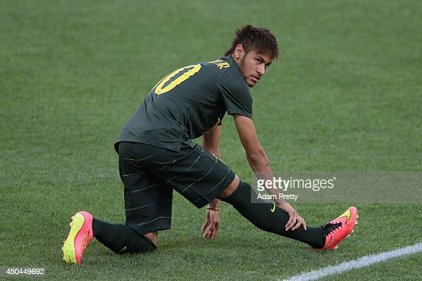 Neymar of Brazil stretches during a Brazil training session ahead of the 2014 FIFA World Cup Brazil opening match against Croatia at Arena de Sao...