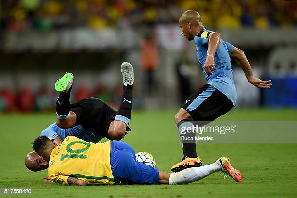 Neymar of Brazil struggles for the ball with Egidio Arevalo Rios and Carlos Sanchez of Uruguay during a match between Brazil and Uruguay as part of...