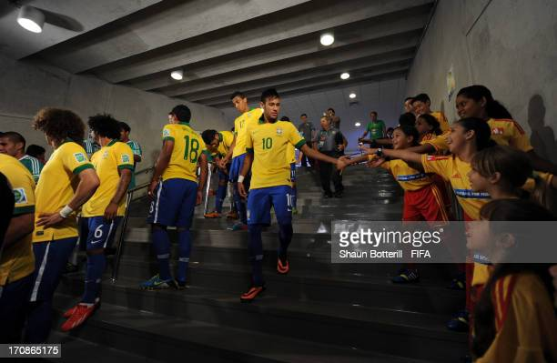 Neymar of Brazil touches hands with mascots on his way to the pitch prior to the FIFA Confederations Cup Brazil 2013 Group A match between Brazil and...