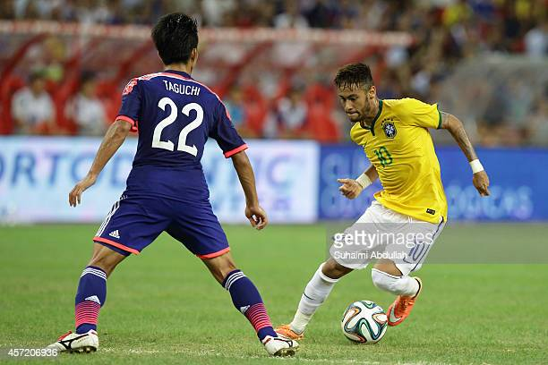 Neymar of Brazil tries to dribble past Taishi Taguchi of Japan during a corner kick during the international friendly match between Japan and Brazil...