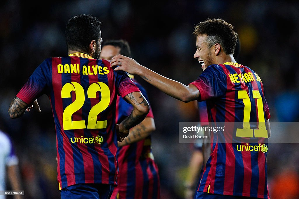 Neymar (R) of FC Barcelona celebrates with his team-mate Dani Alves after scoring his team's fourth goal during the La Liga match between FC Barcelona and Real Valladolid CF at Camp Nou on October 5, 2013 in Barcelona, Spain.