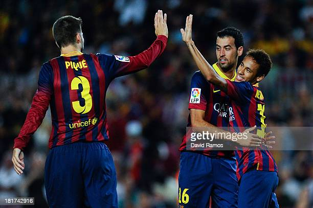 Neymar of FC Barcelona celebrates with his teammates Gerard Pique and Sergio Busquets of FC Barcelona after scoring the opening goal during the La...