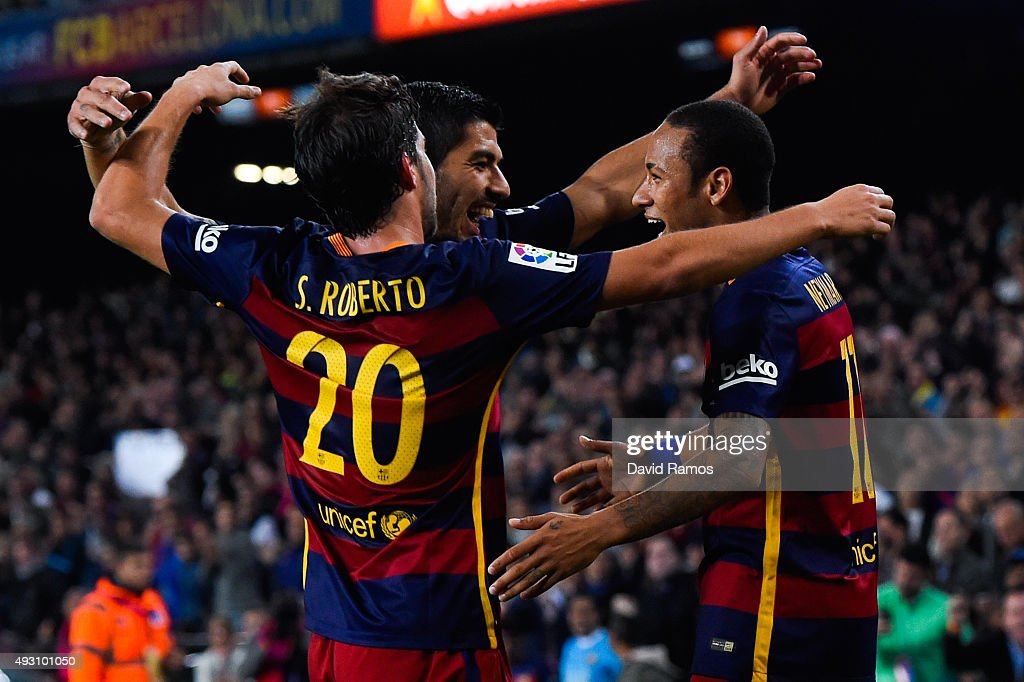 Neymar (R) of FC Barcelona celebrates with his teammates Luis Suarez (C) and Sergio Roberto of FC Barcelona after scoring his team's third goal during the La Liga match between FC Barcelona and Rayo Vallecano at the Camp Nou stadium on October 17, 2015 in Barcelona, Spain.