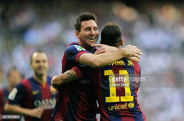 Neymar of FC Barcelona celebrates with Lionel Messi after scoring his team's opening goal during the La Liga match between Real Madrid CF and FC...