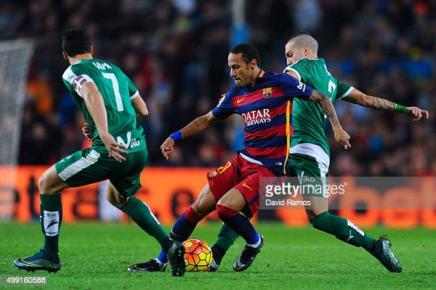 Neymar of FC Barcelona competes for the ball with Ander Capa and Aleksandar Pantic of SD Eibar during the La Liga match between FC Barcelona and SD...