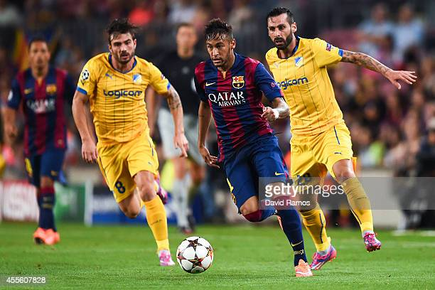 Neymar of FC Barcelona competes for the ball with Cillian Sheridan and Mario Sergio of APOEL FC during the UEFA Champions League Group F match...