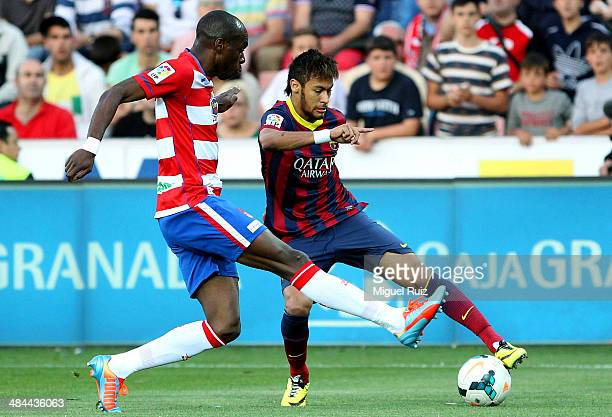 Neymar of FC Barcelona competes for the ball with Nyom of Granada CF during the La Liga match between Granada CF and FC Barcelona at Estadio Nuevo...