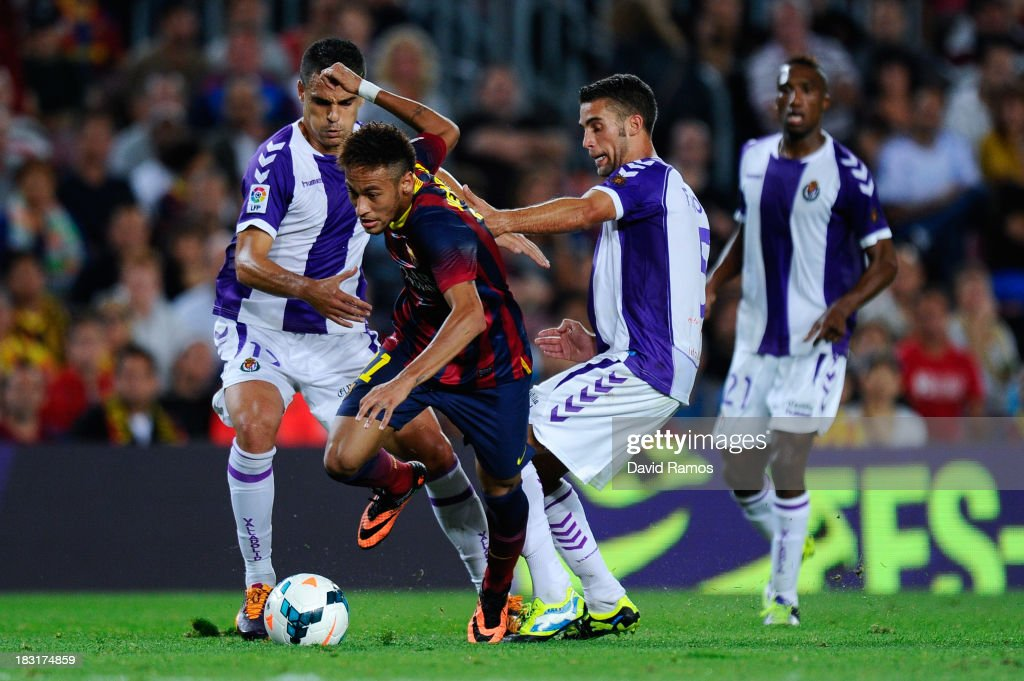Neymar of FC Barcelona duels for the ball with Carlos Pena (L) and Fausto Rossi of Real Valladolid CF during the La Liga match between FC Barcelona and Real Valladolid CF at Camp Nou on October 5, 2013 in Barcelona, Spain.
