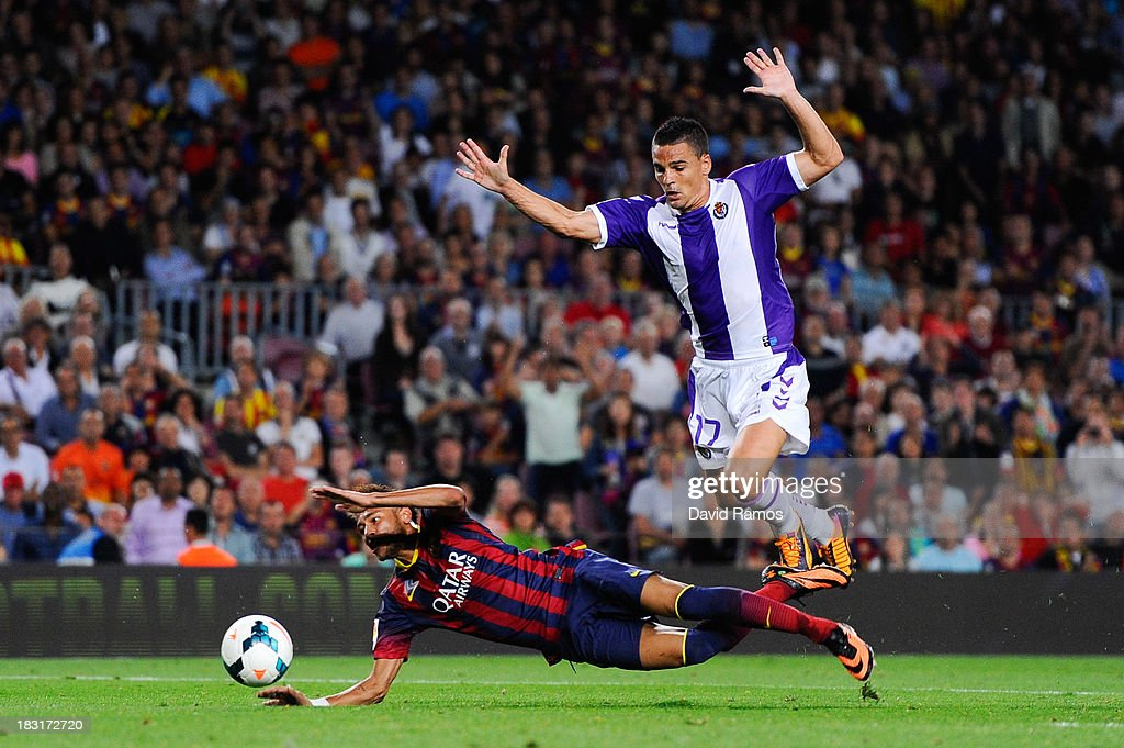 Neymar of FC Barcelona is brought down by Carlos Pena of Real Valladolid CF during the La Liga match between FC Barcelona and Real Valladolid CF at Camp Nou on October 5, 2013 in Barcelona, Spain.