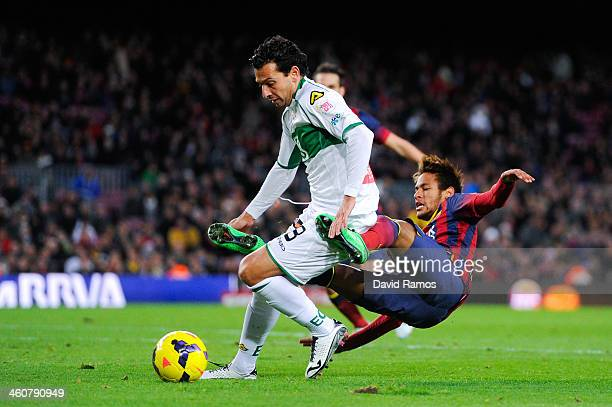 Neymar of FC Barcelona is brought down by Sergio Mantecon of Elche FC during the La Liga match between FC Barcelona and Elche FC at Camp Nou on...