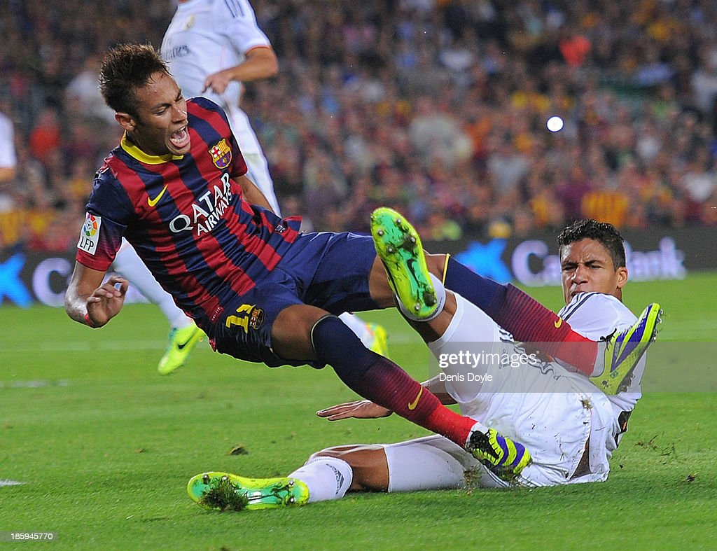 Neymar of FC Barcelona is brought down in a tackle by <a gi-track='captionPersonalityLinkClicked' href=/galleries/search?phrase=Raphael+Varane&family=editorial&specificpeople=7365948 ng-click='$event.stopPropagation()'>Raphael Varane</a> of Real Madrid CF during the La Liga match between FC Barcelona and Real Madrid CF at Camp Nou stadium on October 26, 2013 in Barcelona, Spain.