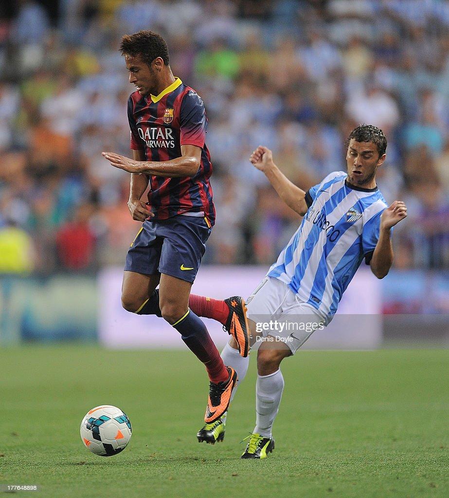 Neymar (L) of FC Barcelona is tackled by Sebastian Fernandez of Malaga CF during the La Liga match between Malaga CF and FC Barcelona at La Rosaleda Stadium on August 25, 2013 in Malaga, Spain.
