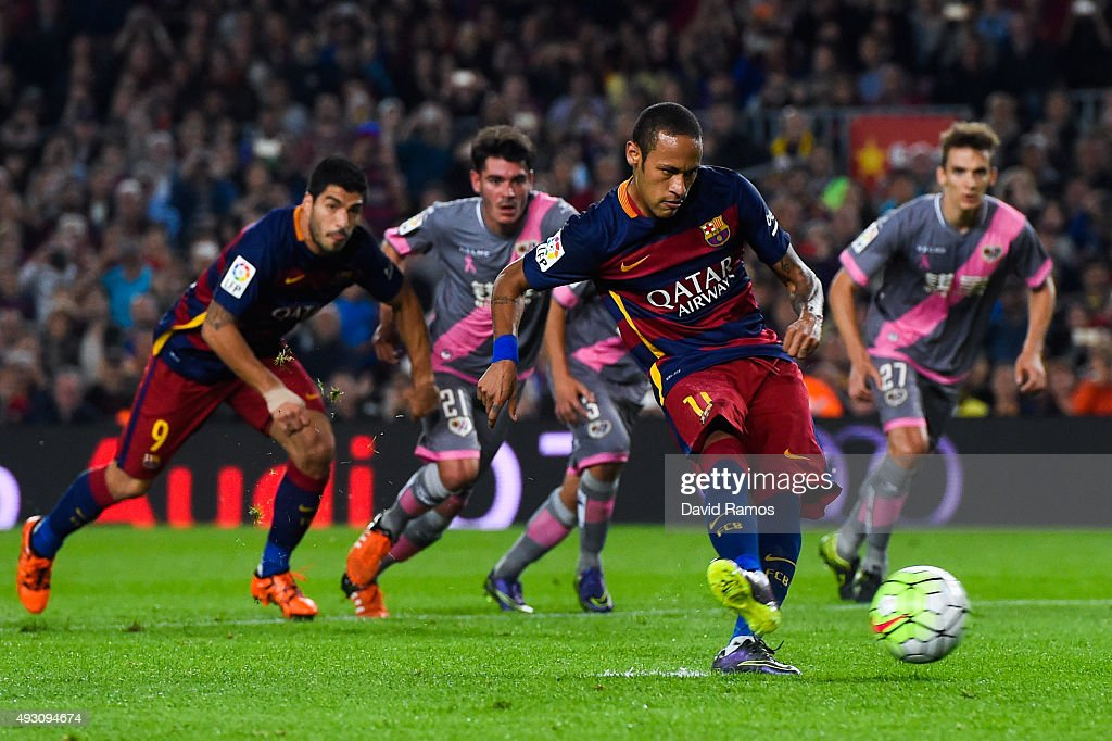 Neymar (L) of FC Barcelona scores his team's first goal from the penalty spot during the La Liga match between FC Barcelona and Rayo Vallecano at the Camp Nou stadium on October 17, 2015 in Barcelona, Spain.