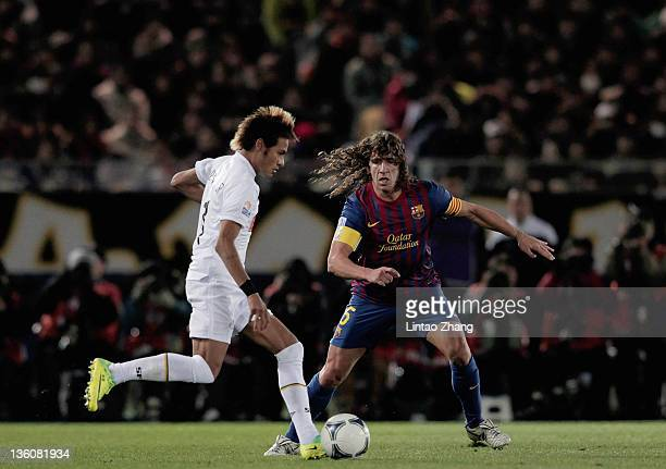 Neymar of Santos IS challenged by Carles Puyol of FC Barcelona during the FIFA Club World Cup Final match between Santosl and Barcelona at the...