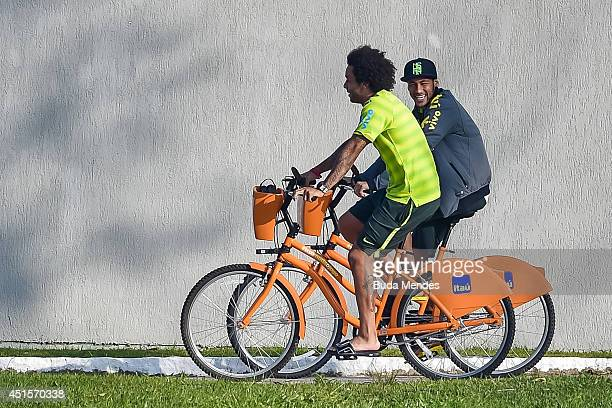 Neymar rides a bike with a Marcelo before a training session of the Brazilian national football team at the squad's Granja Comary training complex on...