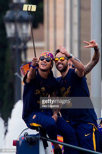 Neymar Santos Jr and Claudio Bravo of FC Barcelona take a selfie as they celebrate on an open top bus during their victory parade after winning the...