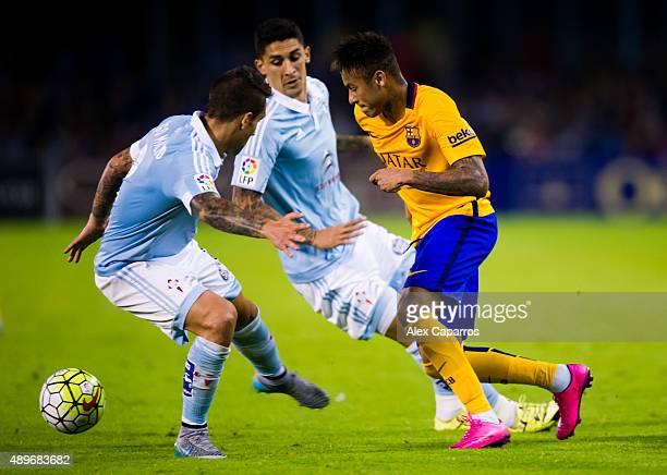 Neymar Santos Jr of FC Barcelona conducts the ball between Hugo Mallo and Pablo Hernandez of Celta Vigo during the La Liga match between Celta Vigo...