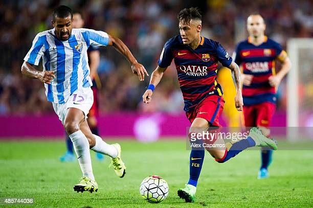 Neymar Santos Jr of FC Barcelona conducts the ball next to Fernando Tissone of Malaga CF during the La Liga match between FC Barcelona and Malaga CF...