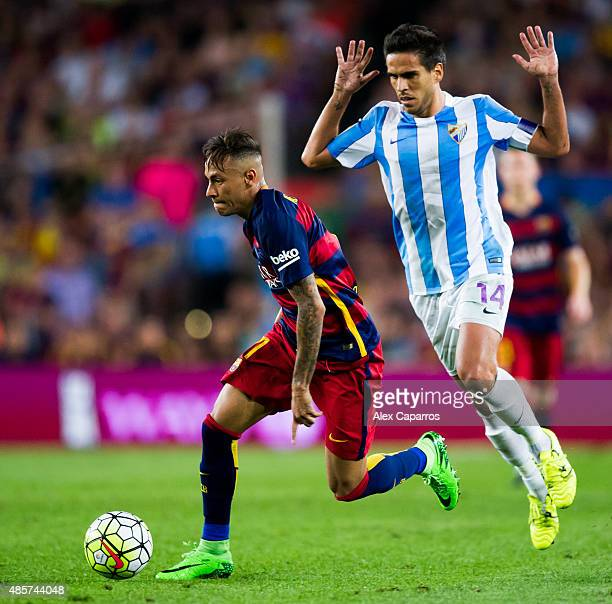 Neymar Santos Jr of FC Barcelona conducts the ball next to Jose Luis Garcia 'Recio' of Malaga CF during the La Liga match between FC Barcelona and...