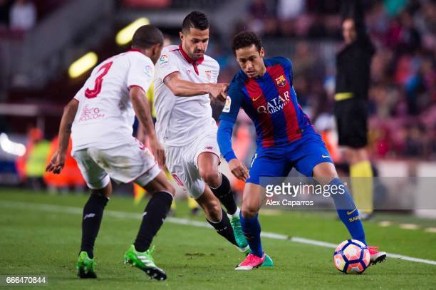 Neymar Santos Jr of FC Barcelona dribbles Victor Machin 'Vitolo' and Mariano Ferreira of Sevilla FC during the La Liga match between FC Barcelona and...