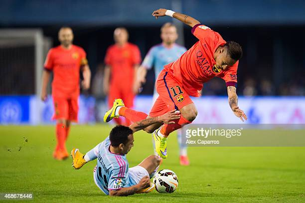 Neymar Santos Jr of FC Barcelona is brought down by Fabian Orellana of Celta Vigo during the La Liga match between Celta Vigo and FC Barcelona at...