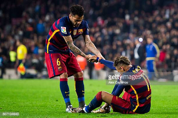 Neymar Santos Jr of FC Barcelona is helped by his teammate Dani Alves as he lays injured after scoring his team's third goal during the Copa del Rey...