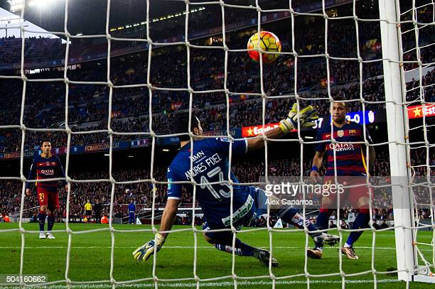 Neymar Santos Jr of FC Barcelona shoots the ball past Andres Fernandez of Granada CF and scores his team's fourth goal during the La Liga match...