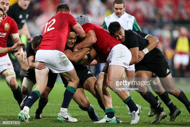 Ngani Laumape of New Zealand is tackled by Owen Farrell and Jonathan Davies of the Lions during the International Test match between the New Zealand...