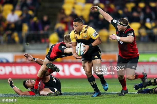 Ngani Laumape of the Hurricanes beats the defence of Richie Mo'unga Jack Goodhue and Wyatt Crockett of the Crusaders during the round 17 Super Rugby...