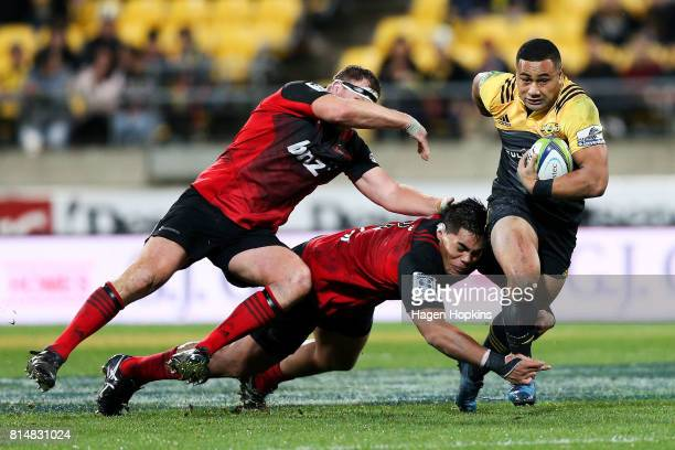 Ngani Laumape of the Hurricanes is tackled by Michael Alaalatoa and Wyatt Crockett of the Crusaders during the round 17 Super Rugby match between the...